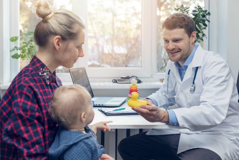 Doktor gibt dem Kind ein Entenspielzeug während eines medizinischen Besuchs lizenzfreie stockbilder
