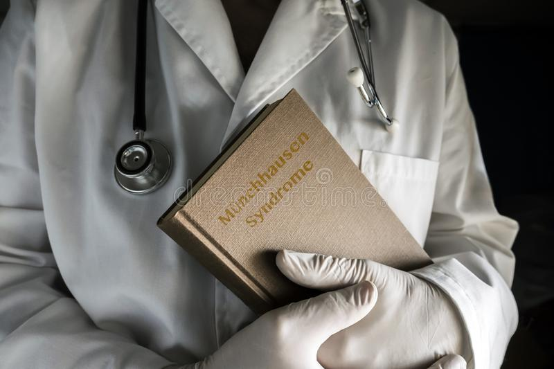Doktor hält in einem Munchausen-Syndrombuch in einem Krankenhaus lizenzfreie stockbilder
