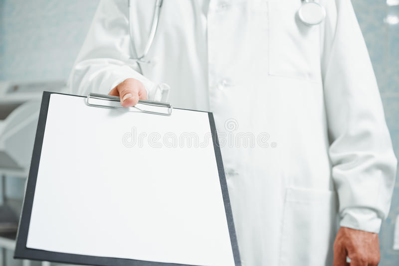 Doktor hält heraus leeres Klemmbrett, Kopieraum lizenzfreie stockfotos