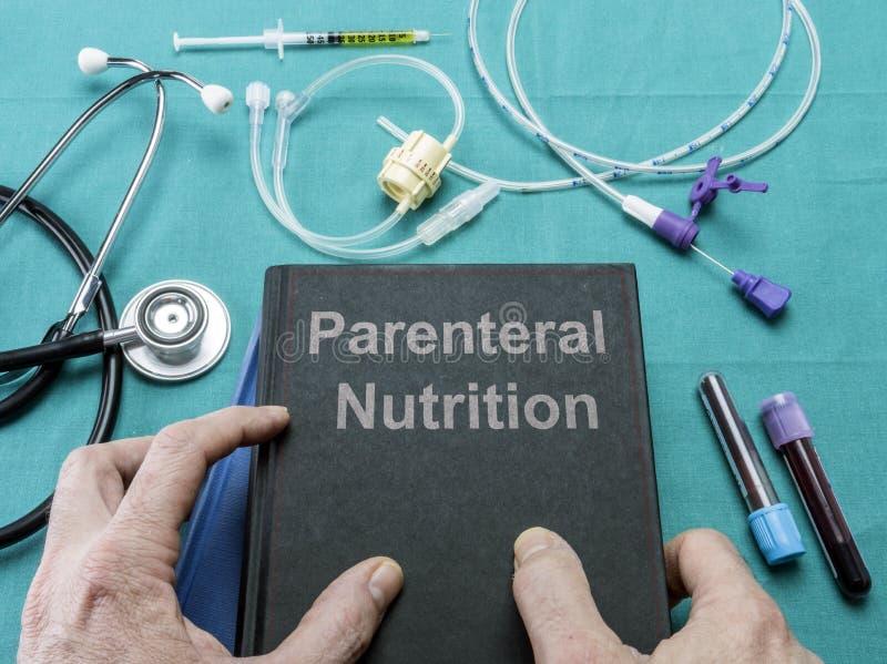 Doktor hält in seinen Händen ein Buch auf der parenteralen Nahrung stockfotos