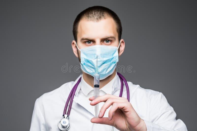 Doktor hält Spritze Mann im weißen Mantel und chirurgischen in der Maske lokalisiert auf Grau Ambulanzdienste und Behandlungskonz stockfotografie