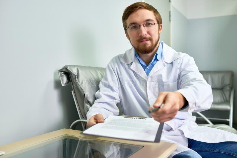 Doktor Handing Pen till patienten arkivfoton