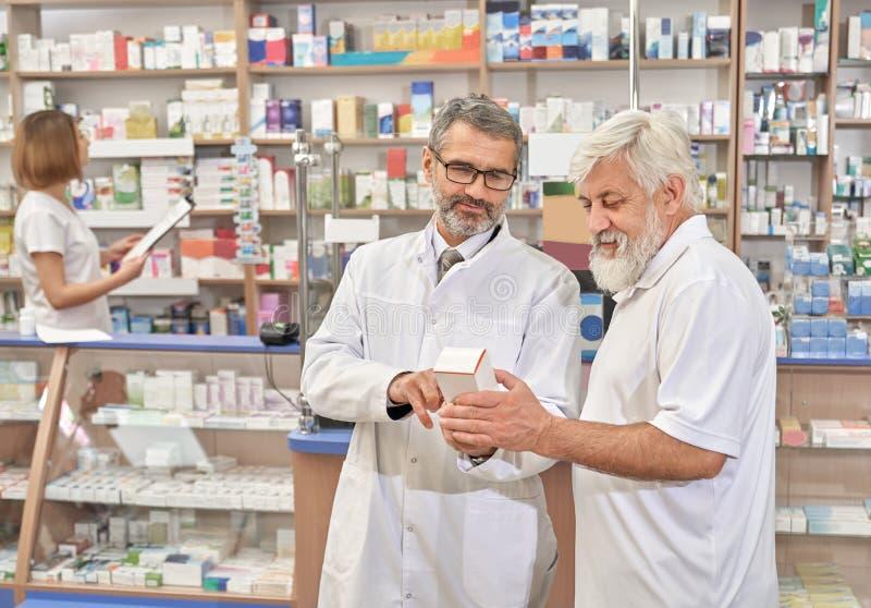 Doktor helfendes pansioner mit Wahl von Medizin lizenzfreies stockfoto