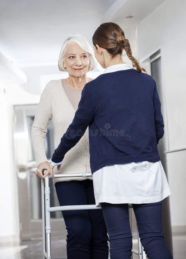 Doktor Helping Senior Patient med Walker In Rehabilitation Cent arkivbild