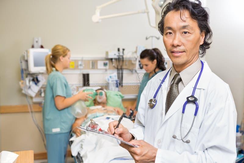 Doktor Holding Clipboard i nödläge fotografering för bildbyråer