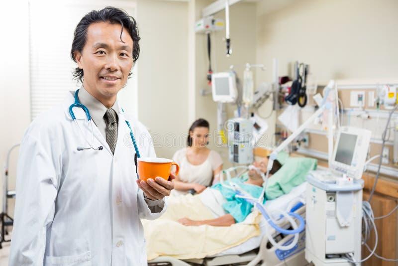 Doktor Holding Coffee Cup med patienten som vilar på royaltyfria bilder