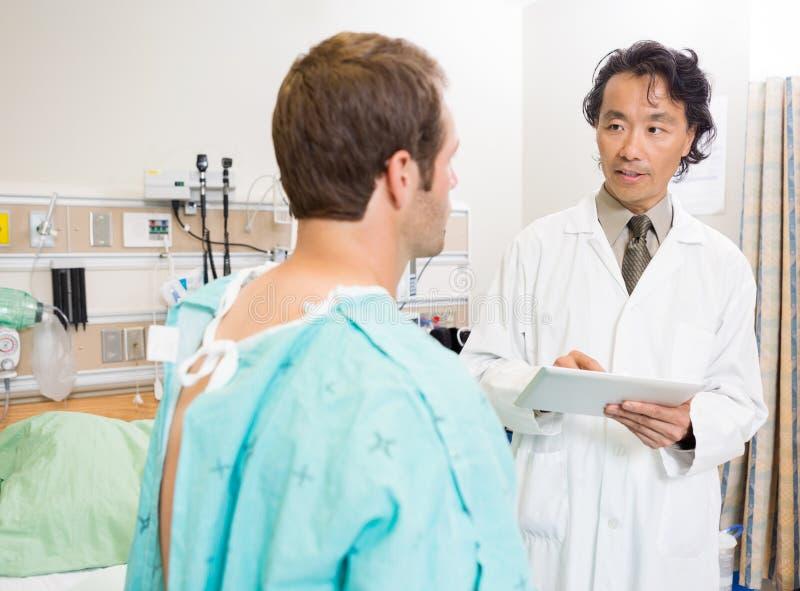 Doktor Holding Digital Tablet bei der Diskussion lizenzfreie stockbilder