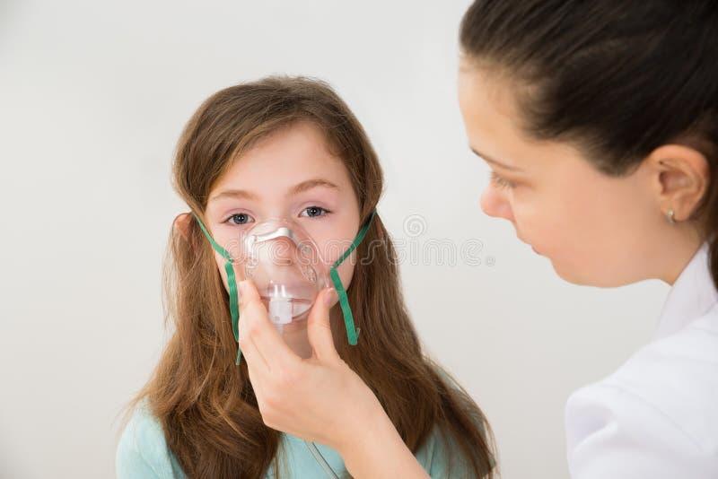 Doktor Holding Inhaler Mask för flickaandning royaltyfri foto