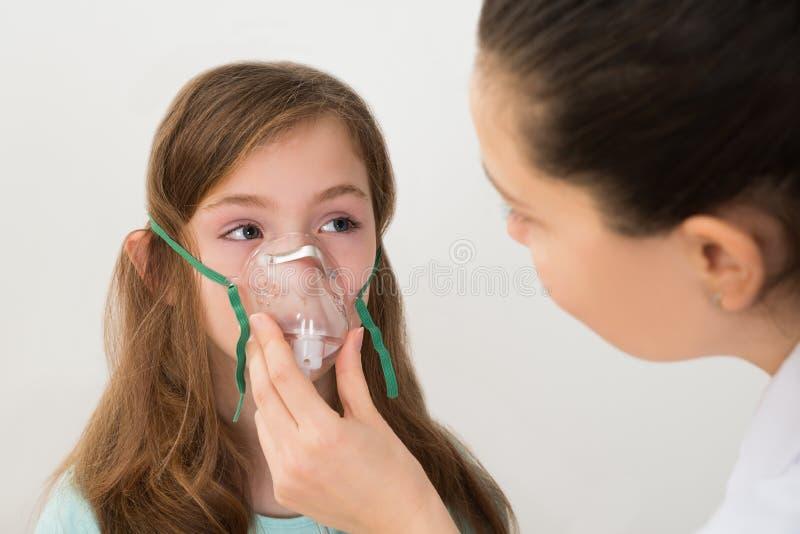 Doktor Holding Inhaler Mask för flickaandning arkivfoton