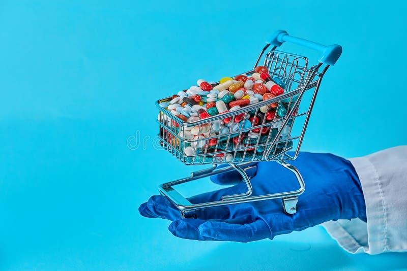 Doktor Holding Shopping Cart med mycket av preventivpillerar arkivfoton
