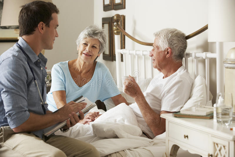 Doktor On Home Visit som diskuterar hälsa av den höga manliga patienten med frun royaltyfri fotografi
