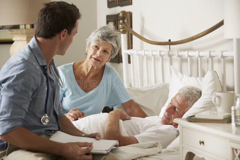 Doktor On Home Visit som diskuterar hälsa av den höga manliga patienten med frun fotografering för bildbyråer