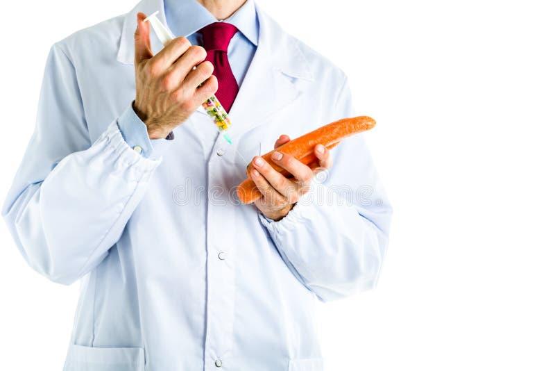 Doktor i det vita laget som gör en injektion till den orange moroten royaltyfria foton