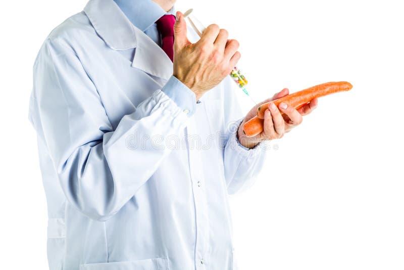 Doktor i det vita laget som gör en injektion till den orange moroten arkivbild