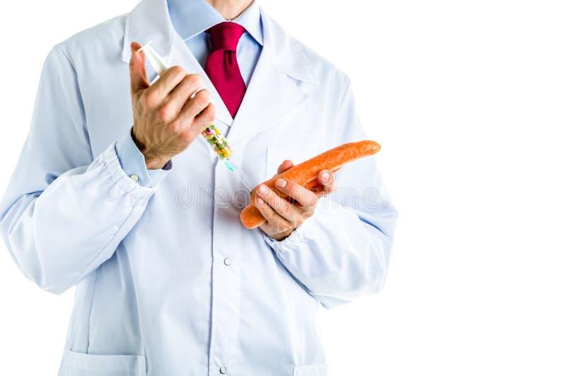Doktor i det vita laget som gör en injektion till den orange moroten arkivbilder