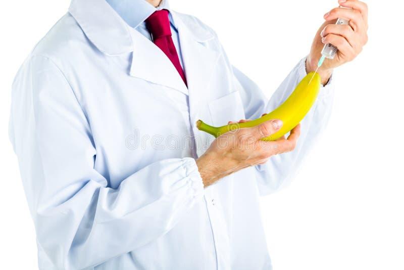 Doktor i det vita laget som gör en injektion till en banan arkivbild
