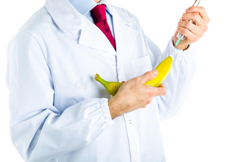 Doktor i det vita laget som gör en injektion till en banan royaltyfri bild
