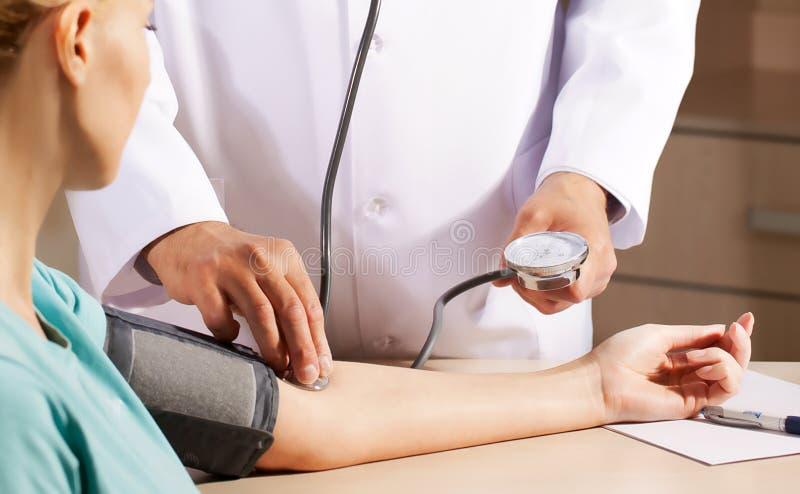 doktor i hans kontor som mäter blodtryck royaltyfri fotografi