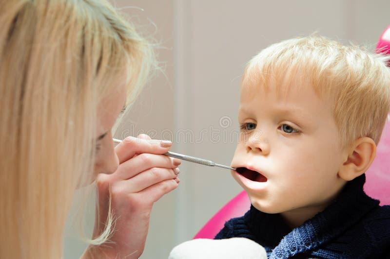 Doktor i likformig som kontrollerar upp kvinnliga tålmodiga tänder för ` s i tand- klinik arkivbild