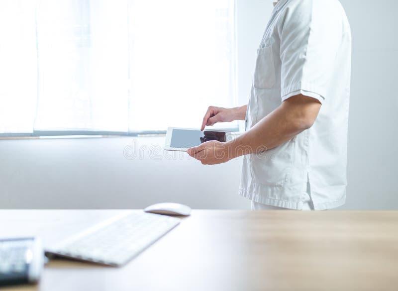 Doktor i likformign genom att använda datorminnestavlan bredvid hans kontorsskrivbord i sjukhus arkivbild