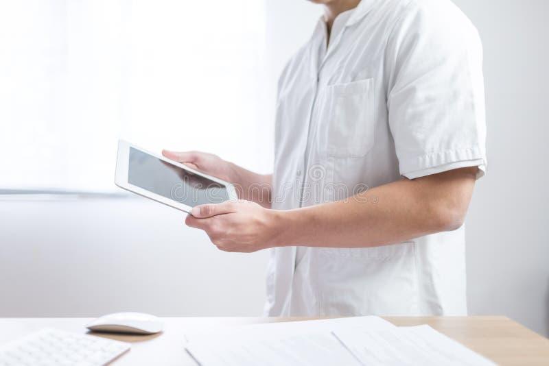 Doktor i likformign genom att använda datorminnestavlan bredvid hans kontorsskrivbord i sjukhus arkivfoto
