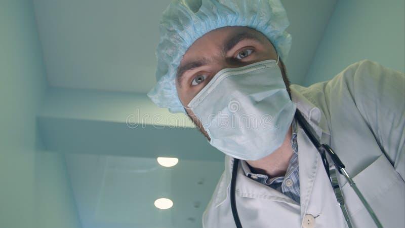 Doktor i maskeringen som ner ser på patienten som kontrollerar hans medvetenhet royaltyfri bild