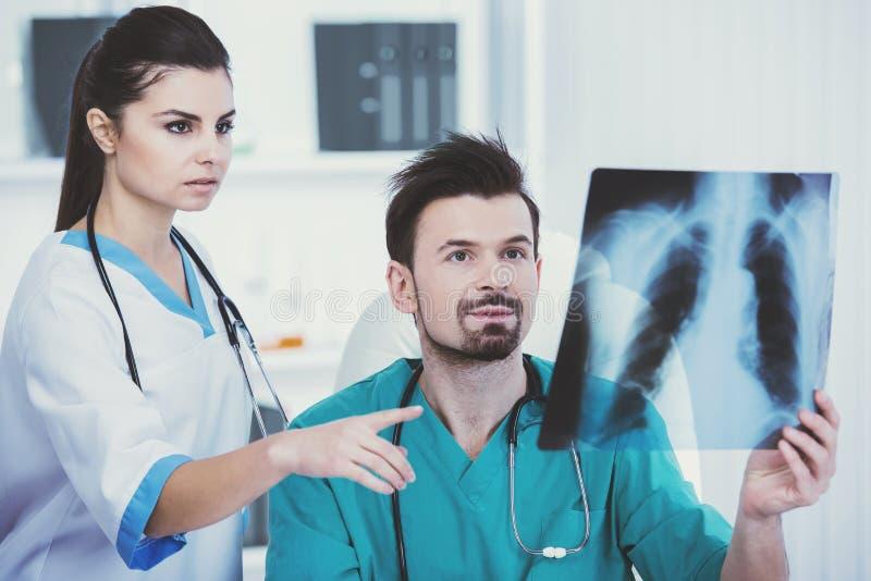 Doktor im grünen medizinischen Kleid hält Röntgen stockbilder