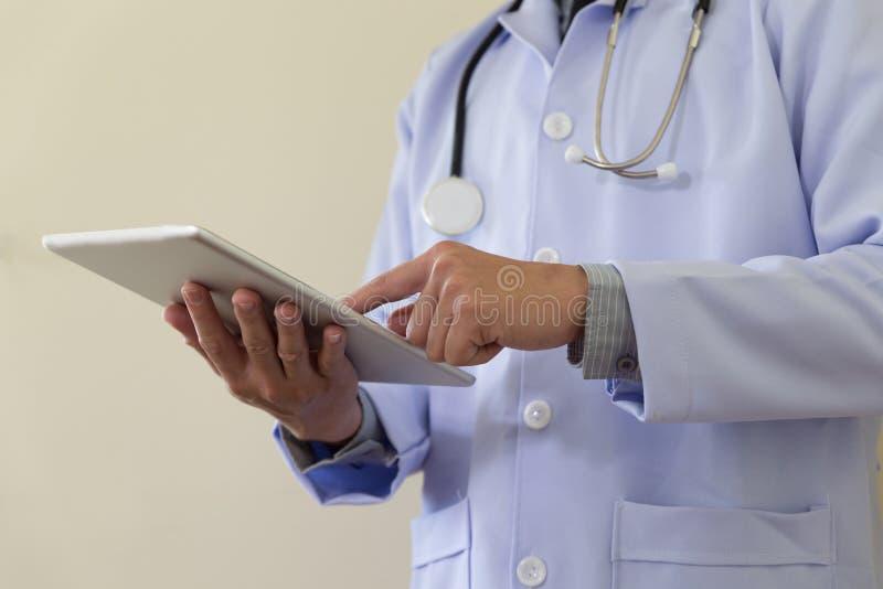 Doktor im weißen Laborkittel unter Verwendung seines Tablet-Computers bei der Arbeit lizenzfreie stockfotografie