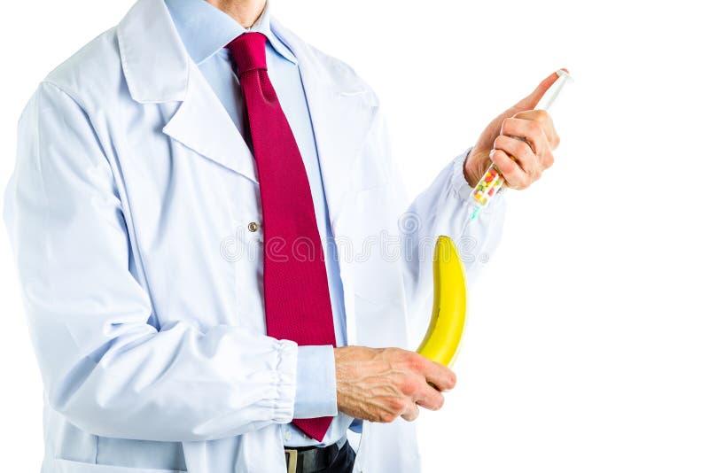 Doktor im weißen Mantel, der einer Banane eine Einspritzung macht stockfotos