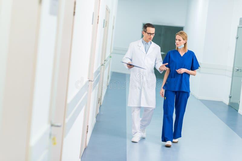 Doktor im weißen Mantel und weiblichen im Chirurgen, die Diagnose bespricht stockfotos