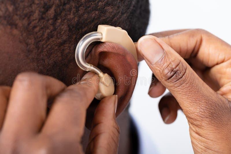 Doktor Inserting Hearing Aid i - patients ?ra royaltyfri fotografi