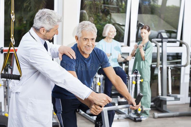 Doktor Instructing Senior Man auf Hometrainer in der Eignungs-Mitte stockbilder
