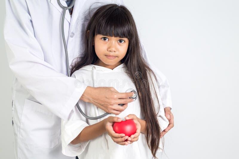 Doktor ist, Herz geformtes kleines Mädchen heilend stockfoto