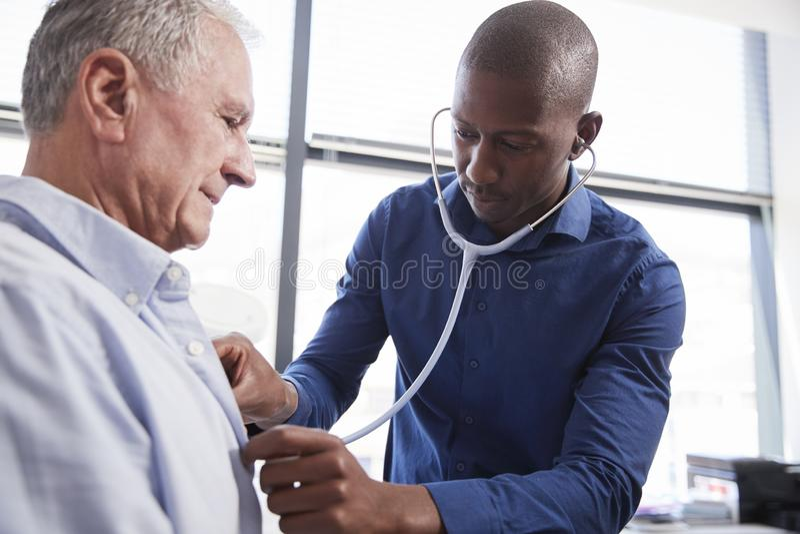 Doktor Listening To Chest av den höga manliga patienten under medicinsk examen i regeringsställning royaltyfria bilder