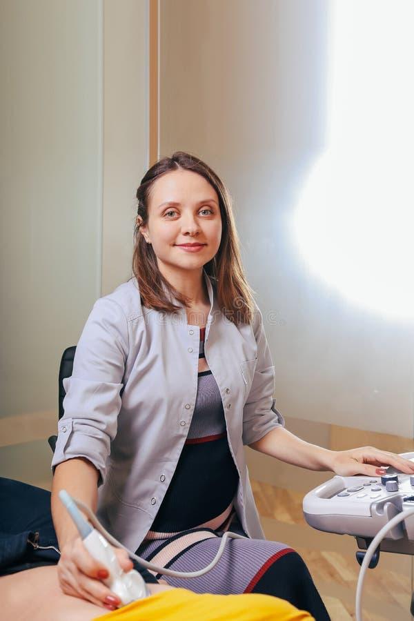 Doktor macht die geduldigen Frauen Abdominal- Ultraschall Ultraschallscanner in den Händen eines Doktors stockbild