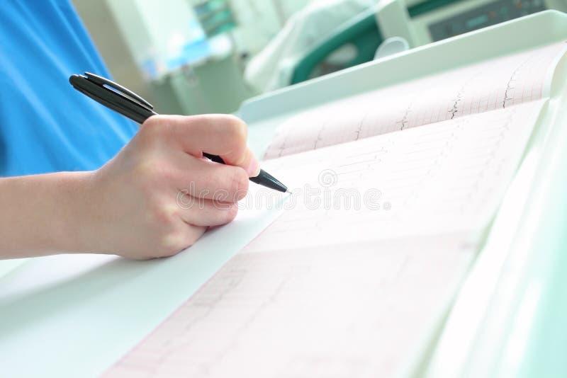 Doktor macht eine Anmerkung Ablesenecg lizenzfreie stockbilder