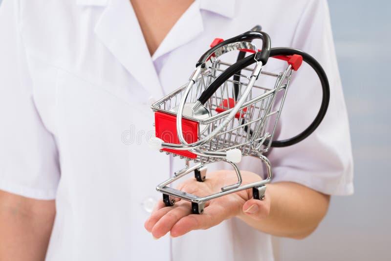 Doktor med den lilla shoppingvagnen och stetoskopet arkivbild