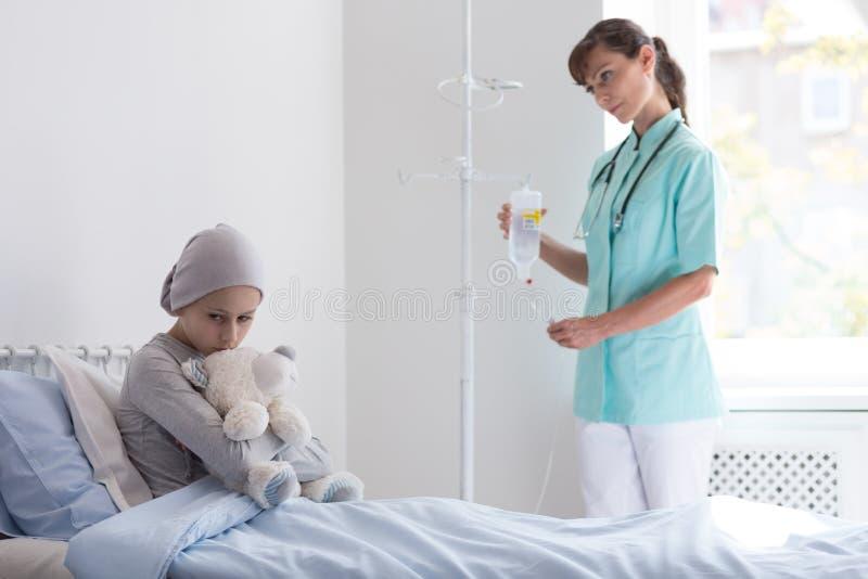 Doktor med droppande som besöker den ledsna sjuka flickan med cancer i sjukhuset royaltyfri bild