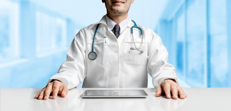 Doktor med minnestavladatoren p? sjukhuskontoret royaltyfria foton