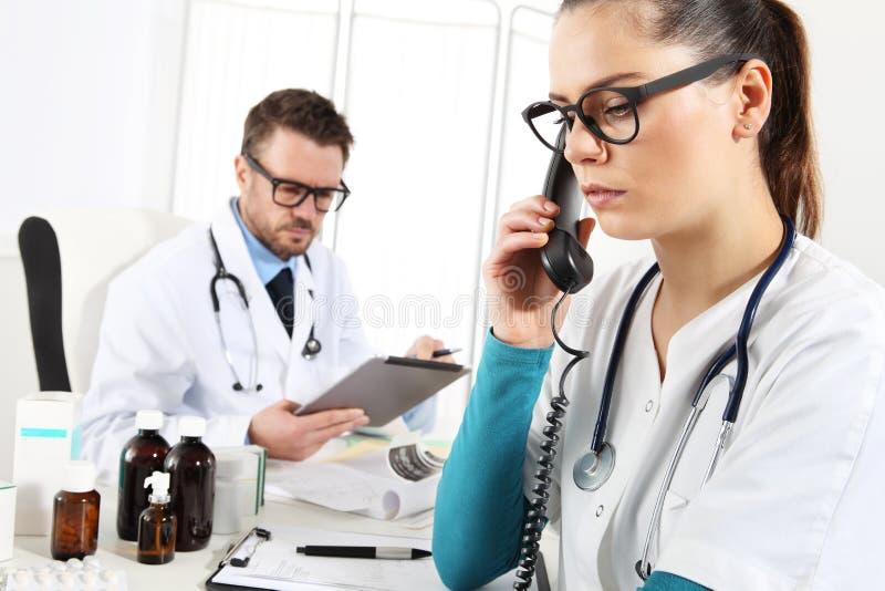 Doktor med minnestavlan och sjuksköterskan på telefonen i medicinskt kontor royaltyfri fotografi