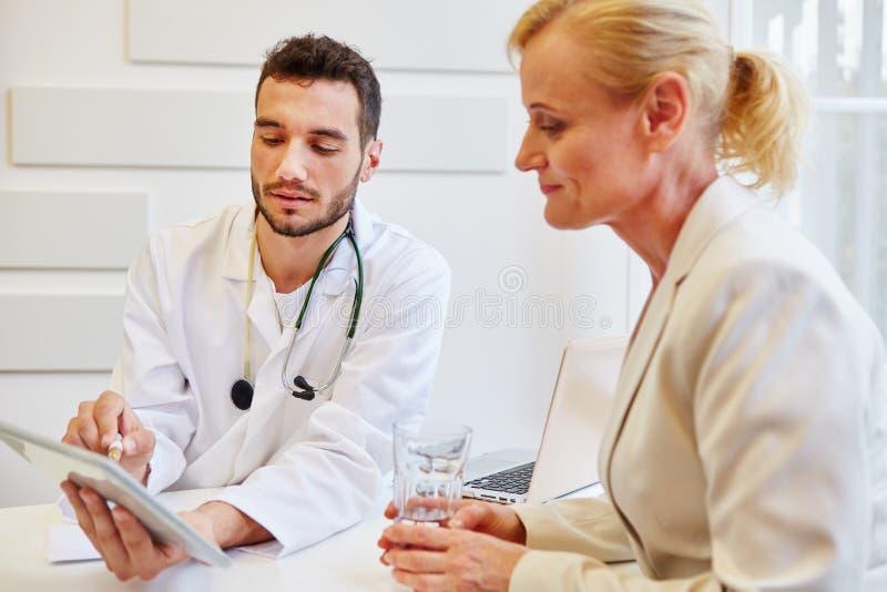 Doktor med minnestavlan som ger rådgivning arkivfoto