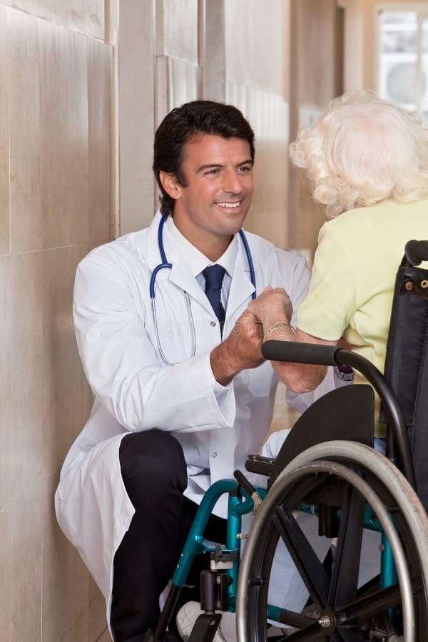 Doktor med patienten på hjulstol royaltyfri bild