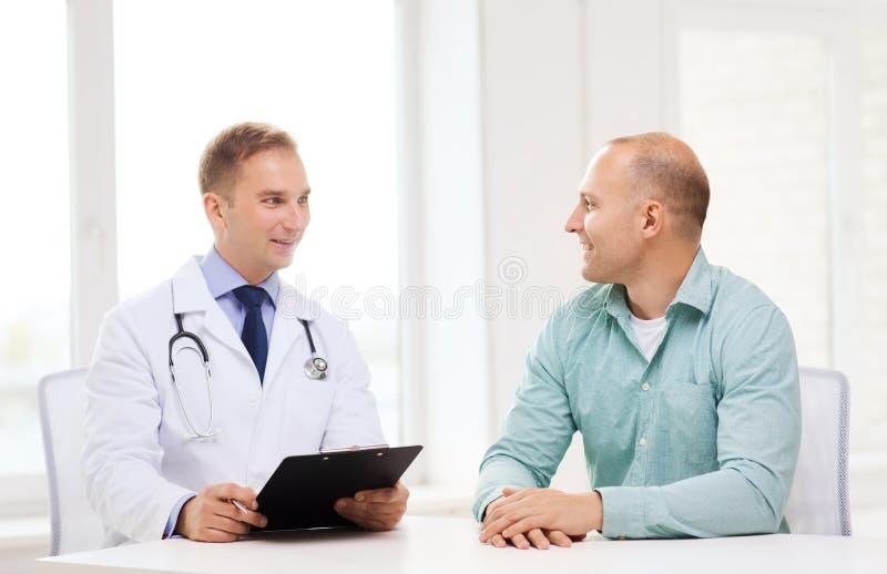 Doktor med skrivplattan och patienten i sjukhus royaltyfri foto