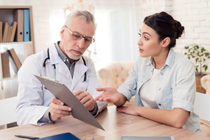 Doktor med stetoskopet och kvinnligpatienten i regeringsställning Doktorn är den träffande diagnosen royaltyfria foton