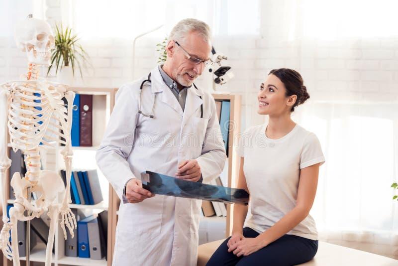 Doktor med stetoskopet och kvinnligpatienten i regeringsställning Doktorn visar röntgenstrålen av höfter royaltyfri bild