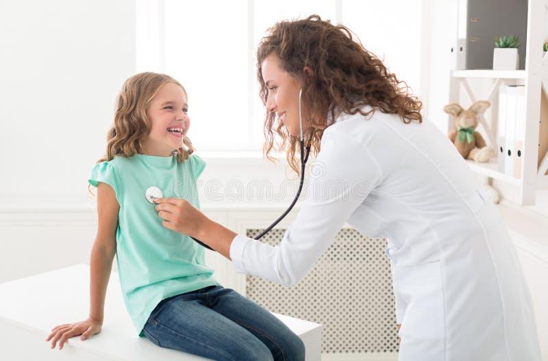 Doktor med stetoskopet som lyssnar till barnandning i sjukhus arkivbild