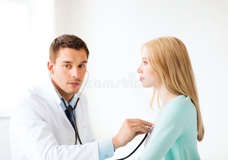 Doktor med stetoskopet som lyssnar till tålmodign royaltyfria bilder
