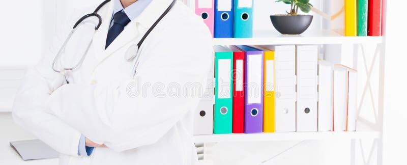 Doktor med stetoskopet som poserar mot bakgrunden av ett medicinskt kontor royaltyfri bild
