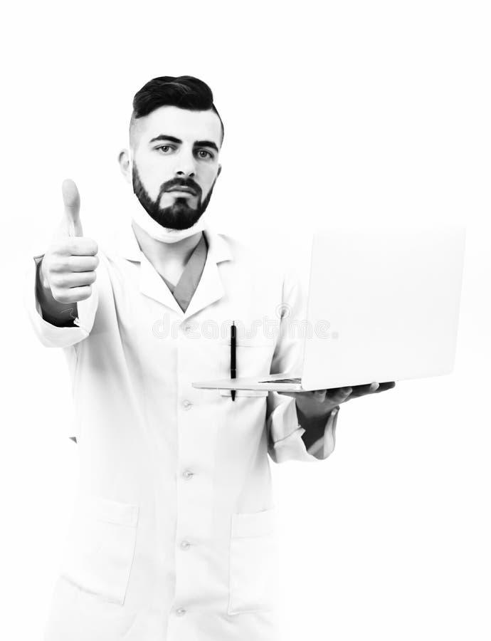 Doktor mit Bart hält weißen Laptop und zeigt sich Daumen stockfotografie