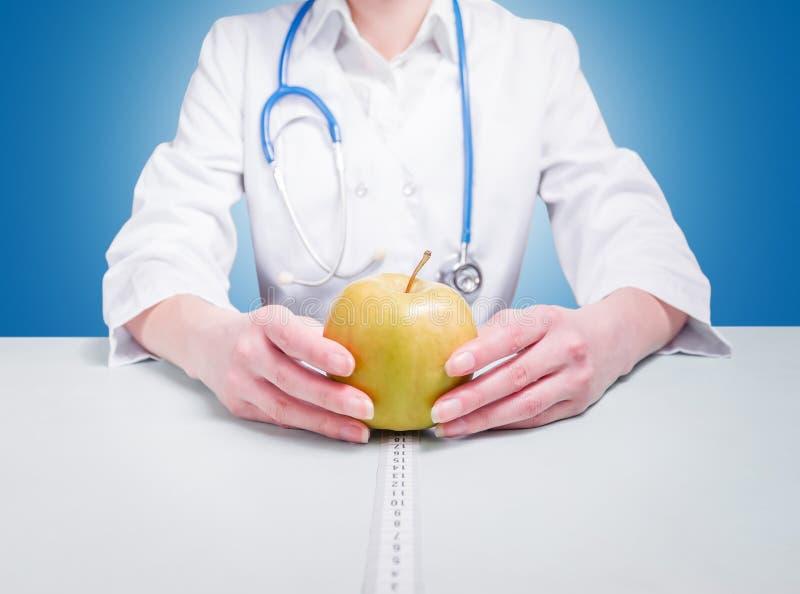 Doktor mit den Äpfeln, die am Tisch sitzen stockfoto